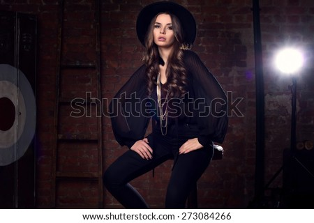 Fashion vogue style portrait of young pretty stylish girl sitting in loft interior on high barchair in black blouse, trousers, hat and boots - stock photo