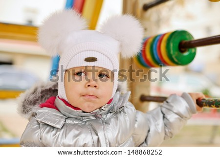 fashion winter girl wearing fur bobble hat on the playground - stock photo