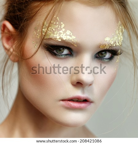 Fashion woman - beauty gilded golden make-up. Luxury young face - stock photo
