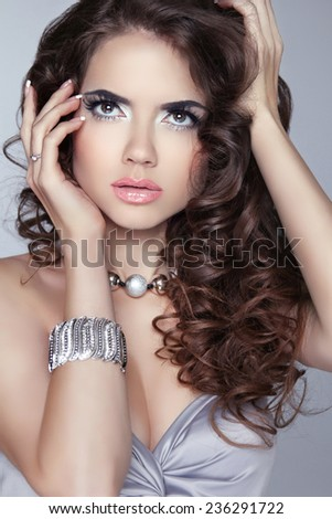 Fashion Woman Beauty Portrait. Makeup. Long wavy shine hair. Brunette attractive girl model posing isolated on gray background. - stock photo