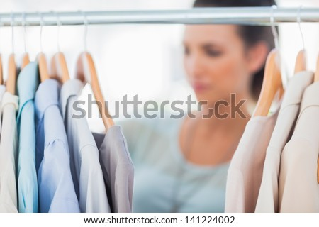 Fashion woman choosing clothes on clothes rail in a studio - stock photo