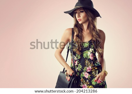 fashion woman holding handbags wearing jumpsuit, hat, wedges shoes. Studio shot - stock photo