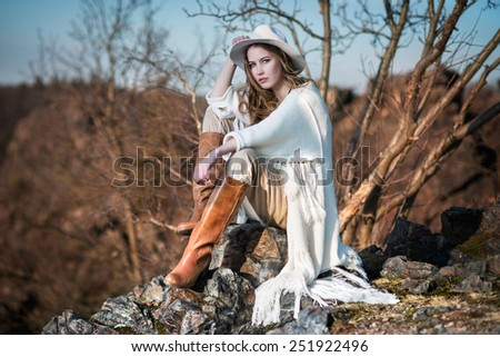 Fashion woman in country style sitting on the canyon rock - stock photo