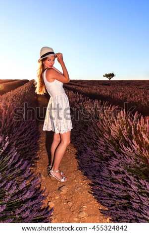 Fashion woman in dress with a straw hat in the lavender fields.  - stock photo