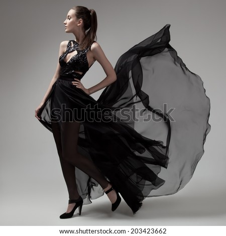 Fashion woman in fluttering black dress. Gray background. - stock photo