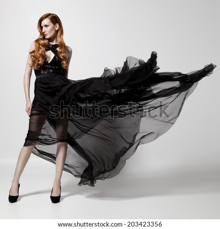 Fashion woman in fluttering black dress. White background. - stock photo