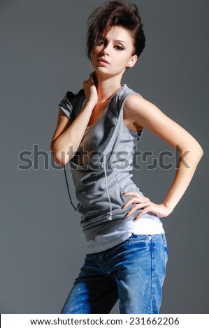 fashion woman in jeans posing on gray background - stock photo