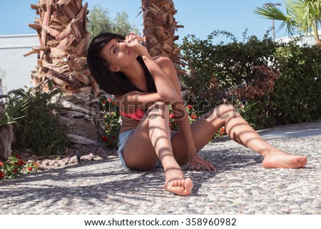 Fashion woman in jeans shorts and pink bra posing on the beach. Outdoors lifestyle - stock photo