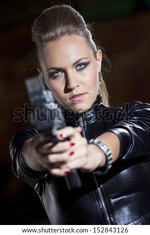 fashion woman in leather catsuit holding a gun at the camera - stock photo