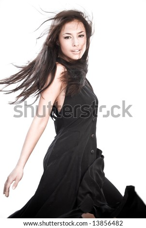 fashion woman in motion, wearing black dress, studio shot - stock photo