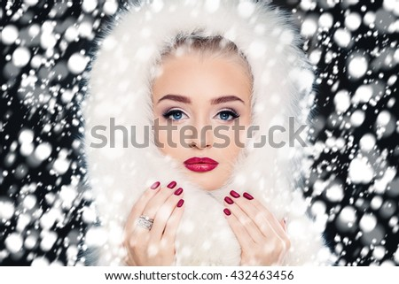 Fashion Woman on Snowfall Winter Background