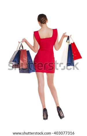 Fashion woman portrait isolated. White background. Girl hold shopping bags. Red dress. female beautiful model