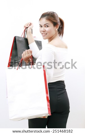Fashion woman portrait isolated. White background. Happy girl hold shopping bag