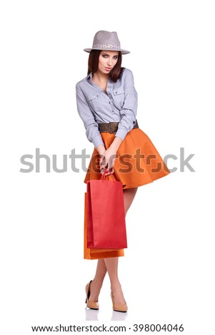 Fashion woman portrait isolated. White background. Happy girl hold shopping bag.