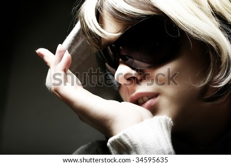 Fashion woman portrait wearing sunglasses on dark background - stock photo