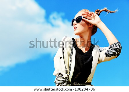 Fashion woman posing over blue sky. - stock photo