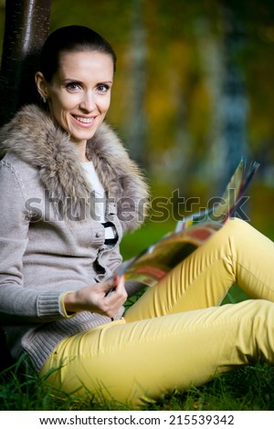 Fashion woman reading  magazine outside in evening park. Student sitting on green grass over tree.