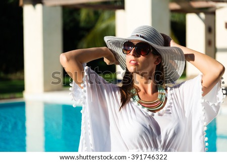 Fashion woman relaxing at luxury resort spa pool. Fashionable caucasian model wearing sun hat, sunglasses and white summer dress. - stock photo