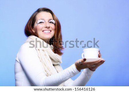 Fashion woman stylish winter makeup holding cup of hot drink beverage enjoying coffee time copyspace blue background