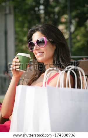 Fashion woman taking coffee after shopping.   Relaxed girl sitting on a bench in city park with white bags.