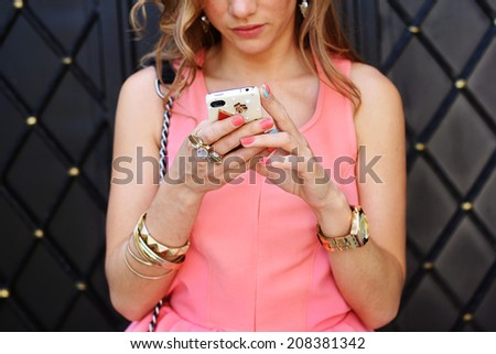 fashion woman using a smart phone outdoor closeup in light pink dress - stock photo