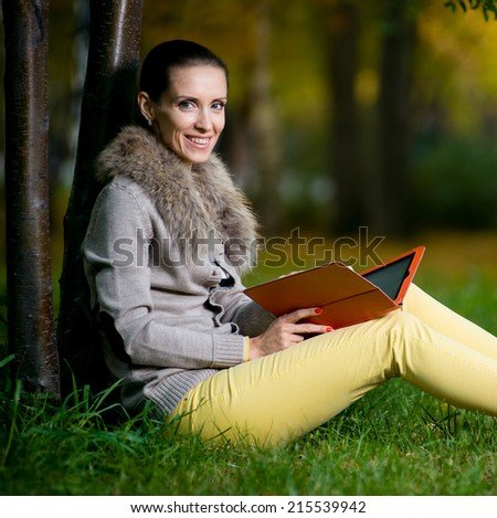 Fashion woman using a tablet computer outside in evening park. Student sitting on green grass over tree.