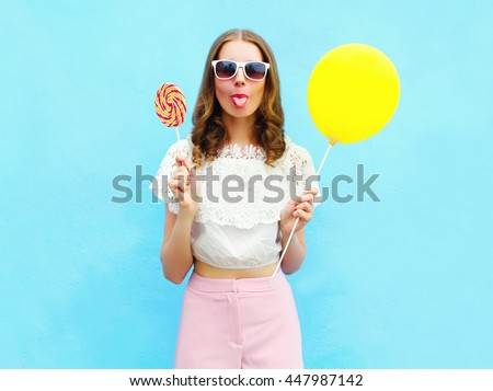 Fashion woman with air balloon and lollipop having fun over colorful blue background - stock photo