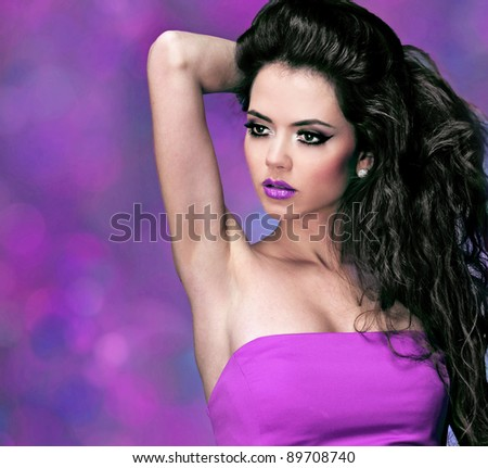 Fashion woman with long black curly hair over purple - stock photo