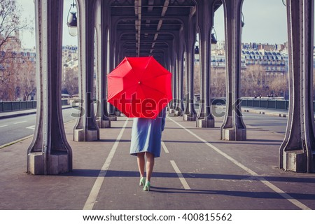 fashion woman with red umbrella walking on the street in Paris - stock photo