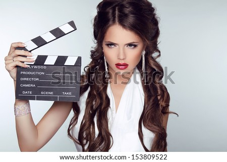 Fashion woman with sexy red lips holding cinema clap. Super star model shot - stock photo