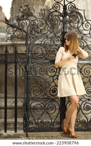 Fashion woman with smart phone outdoors on the street exploring old town european city Gdansk Danzig