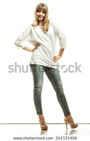 Fashion. Young blonde woman denim pants white bat sleeve top high heels. Female model posing in full length isolated - stock photo