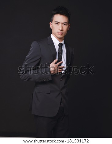 Fashion young businessman black suit casual tie on black background