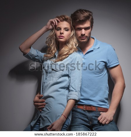fashion young couple posing for the camera against gray studio wall - stock photo