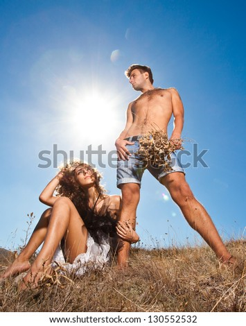 Fashion young couple standing together in a wheat field