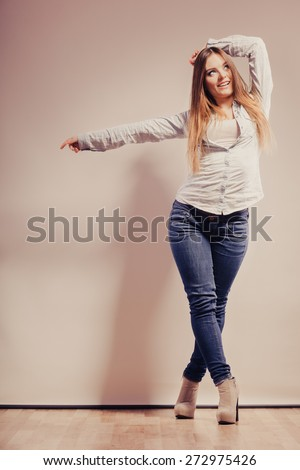 Fashion. Young long hair fashionable woman jeans pants shirt. Female model posing in full body filtered photo