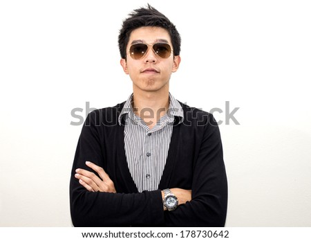 Fashion young man holding his fashionable sunglasses on gray background