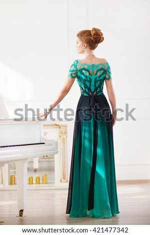Fashion young pretty redhead lady playing grand piano - stock photo