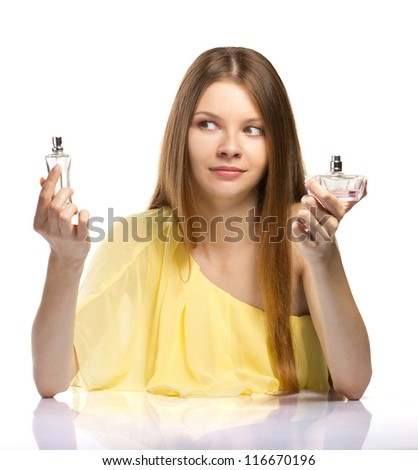 fashion young woman trying to choose a perfume on white background - stock photo