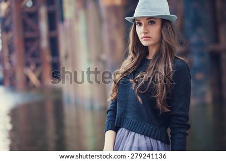 Fashion young woman wearing hat at riverside - stock photo