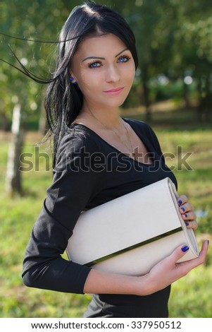 Fashion young woman with a beige clutch in hands