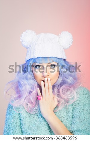 Fashion young woman with blue, purple and pink hair luscious wavy mid-length hair in white beanie and mint green sweater. Beauty makeup fashion portrait, retouched, studio light, vertical, copy space - stock photo