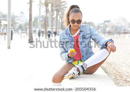 Fashionable and attractive african american teenager girl sitting on the wall a beach in a destination city using a smartphone while roller skating. Recreational technology lifestyle, outdoors. - stock photo