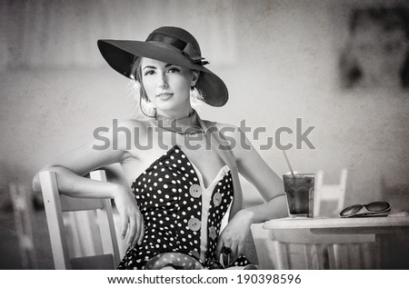Fashionable attractive lady with hat and scarf sitting in restaurant, indoor shot. Young woman posing in elegant scenery, black and white. Art photo of elegant sensual woman relaxing, vintage style - stock photo