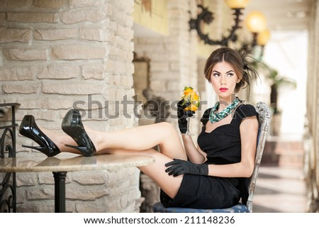 Fashionable attractive young woman in black dress sitting comfortable in restaurant. Beautiful brunette relaxing with legs on table in vintage scenery with a juice glass. Attractive lady with gloves - stock photo