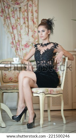 Fashionable attractive young woman in black dress sitting in restaurant. Beautiful brunette posing in elegant vintage scenery with a cup of coffee. Attractive lady creative haircut, luxurious interior - stock photo