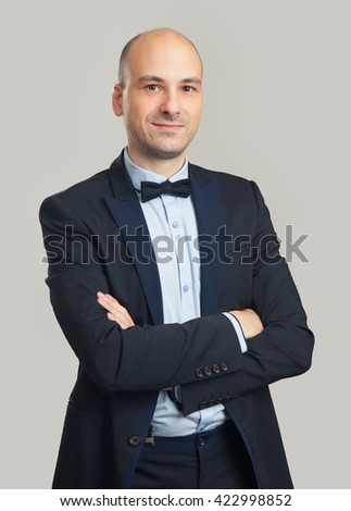 fashionable bald man wearing black suit and bow tie. Isolated on gray - stock photo