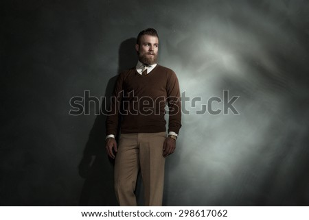 Fashionable bearded young man standing against a grey wall with offset highlight and copyspace
