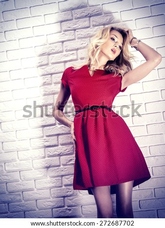 Fashionable beautiful blonde woman posing in red dress over white bricks wall. - stock photo