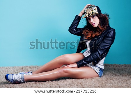 Fashionable beautiful brunette woman posing in studio, over blue background, looking at camera